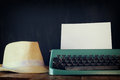 Vintage typewriter with blank page next to fedora hat Royalty Free Stock Photo