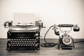 Vintage typewriter and telephone a on a table Stock Photos