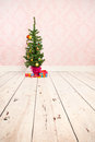 Vintage wall and wooden floor with christmas tree plinth little gifts Royalty Free Stock Images