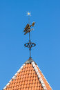 Vintage weather vane cock bird on the red roof a above blue sky Royalty Free Stock Images