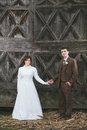 Vintage wedding couple posing bride and groom dressed in dress and suit holding hands with wooden door behind them Stock Image