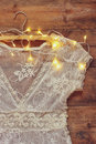 Vintage white crochet lace top on hanger with garland lights on wooden background