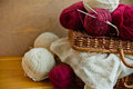 Vintage wicker basket balls clews of red white wool yarn, piece of knitted needlework on wood table, knitting, crafts, hobby conce