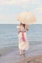 Vintage woman on beach with parasol Royalty Free Stock Photo
