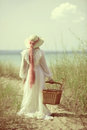 Vintage woman at the beach with picnic basket Royalty Free Stock Photo