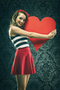 Vintage woman in red dress embraced big paper heart Royalty Free Stock Photo