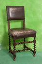 Vintage wood and leather chair on a green background Royalty Free Stock Image