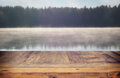 vintage wooden board table in front of abstract photo of misty and foggy lake at morning/evening.