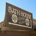 A vintage wooden frame bath house sign bathhouse against blue sky Royalty Free Stock Image