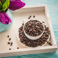 Vintage wooden tray with porcelain cup full of coffee beans and pink flowers on shabby chic mint background, top view Royalty Free Stock Photo