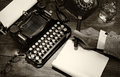 Vintage writer closeup of a at his desk with a typewriter rotary telephone glass of whiskey and a cigar black and white toned Royalty Free Stock Photo