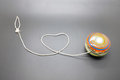 Vintage yoyo with twine rolling in heart shape over grey background Stock Photos