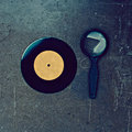 Vinyl record and magnifier on wooden table Royalty Free Stock Photography