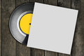 Vinyl record with white blank package on wood background Stock Images