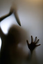 Violence against women shadow of attacker with knife though smoked window Royalty Free Stock Photos