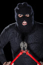 Violent felon a burglar wearing a balaclava holding huge wire cutters over black background Stock Image
