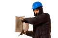 Violent hooligan brandishing a wooden chair teenage in hoodie and hardhat raising it above his shoulder as he prepares to attack Stock Image