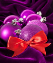 Violet Christmas balls and red bow Stock Image