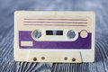 Violet compact cassette with magnetic tape format for audio recording and playback. MC on gray wooden background. Soft Royalty Free Stock Photo