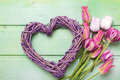 Violet decorative heart and bright pink spring tulips flowers