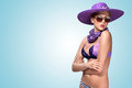 Violet summer a beautiful sexy girl standing in bikini stylish hat and sunglasses Royalty Free Stock Photos