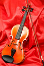 Violin and bow on red silk Royalty Free Stock Image