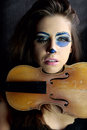 Violin detail view of young girl with and scary makeup Royalty Free Stock Image