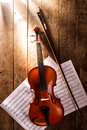 Violin and notes with bow handdrawn under dramatic light over retro wooden table Royalty Free Stock Images
