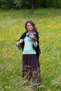 Violinist on a meadow full of flowers, Young girl playing music instrument. Royalty Free Stock Photo