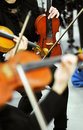 Violinists at an orchestra recital or concert view across the hands of playing with focus to a single instrument in the background Stock Photo
