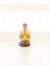 Virasana yoga gym colorful dressed male repeating exercises in a white room with window background Stock Image