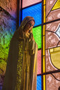 Virgin mary statue with colorful stained glass in background in choachi colombia Stock Image