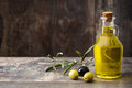 Virgin olive oil in a crystal bottle on wood Royalty Free Stock Photo