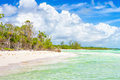 Virgin tropical beach with waves of turquoise water in cuba and trees near the at cayo coco coco key on a summer day puffy white Stock Photos