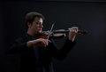 Virtuoso teen violinist male on dark background Royalty Free Stock Images