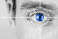 Vision concept with a greyscale image of a mans eye with a crosshair focused on his iris which has been selectively colored blue Stock Photos