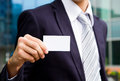 Visit card in hand young businessman holding and standing the front of office building Stock Photo