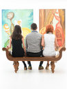 Visit at a contemporary museum back view of three young people sitting on wooden bench in admiring large paintings Royalty Free Stock Photos