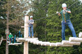 Visitors in adventure park clambering with ropes wear protective Royalty Free Stock Photo
