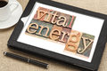 Vital energy typography on tablet text in letterpress wood type blocks a digital with cup of coffee Royalty Free Stock Image