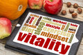 Vitality concept on digital tablet or vital energy word cloud a with apples pumpkin and hazelnuts Stock Photos
