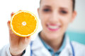 Vitamin happy female nurse or doctor holding an orange Royalty Free Stock Photos