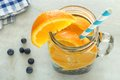 Vitamin water with oranges and blueberries in mason jar a straw downward view on white marble Stock Image