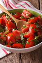 Vitaminic tomato salad with herbs close up in a bowl vertical on the table Royalty Free Stock Photo