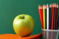 Vitamins for art close up of big green apple on stack of copybooks with colorful pencils near by Stock Image