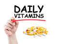 Daily vitamins concept made on transparent wipe board with a hand holding a marker Royalty Free Stock Image