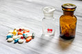 Vitamins and supplements. Pills and pill bottle on grey wooden table background