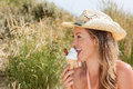 Vivacious beautiful blond enjoying an ice cream cone at the beach during her summer vacation profile view in a sunhat with a sand Royalty Free Stock Photo