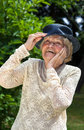 Vivacious elderly lady wearing a hat and elegant lace top laughing outdoors in a summer garden Royalty Free Stock Images