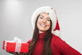 Vivacious happy woman with a christmas gift wearing red festive santa hat in her hand laughing at the camera head and shoulders Royalty Free Stock Images